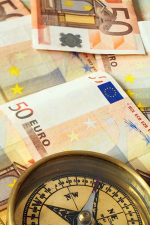 50 euro: A compass, its needle pointing north, on a pile of 50 euro notes, symbolising investment being on track.