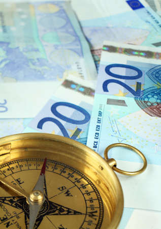 20 euro: A compass with the needle pointing south, on a pile of 20 euro banknotes. Clearly, something is going in the wrong direction Stock Photo