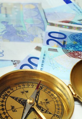 20 euro: A compass, its needle indicating north, on a pile of 20 euro notes, symbolising a good investment decision or some financial success.