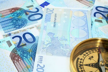 20 euro: A compass, showing North, on a background of 20 euro banknotes - symbolic of finances being on the right course.  Stock Photo