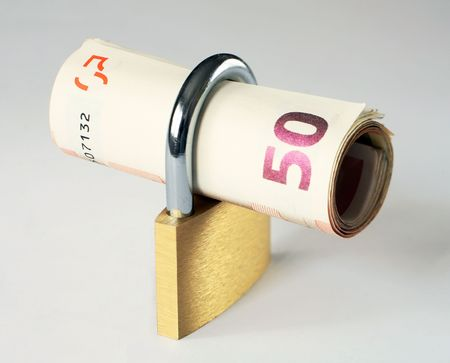 bankroll: A roll of 50 euro notes in a closed padlock, symbolising financial security. Diagonal depth of field to keep the notes in focus across the image.