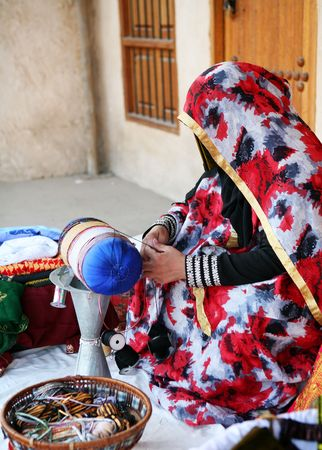 modesty: A Qatari woman at work producing traditional handicrafts during the annual Doha Cultural Week. Stock Photo