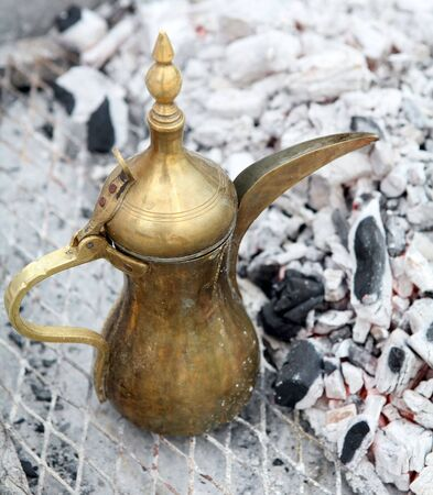 kept: A traditional Gulf brass dallah coffee pot, the Arab symbol of welcome, being kept warm beside burning charcoal.