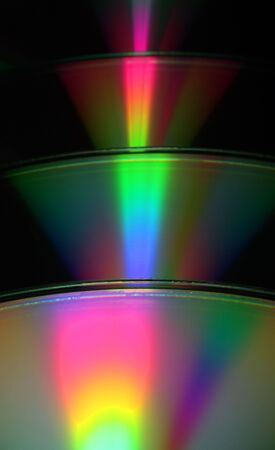 spectra: An abstract view of CDs refracting light in rainbows. Stock Photo