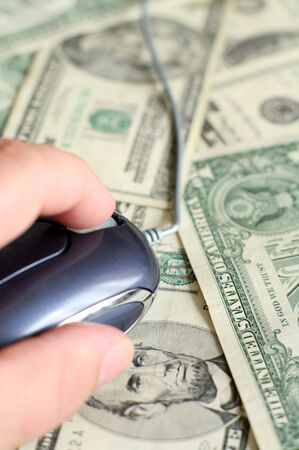 Using a computer mouse on an array of US banknotes, symbolic of making or spending money using computers photo