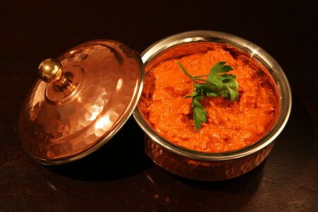 An authentic Indian copper-clad serving dish with  butter chicken curry, garnished with a coriander (cilantro) leaf, on a dark wood table. photo