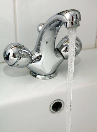grifo agua: Un toque en cuartos de ba�o con el agua corriendo.
