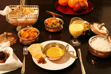 veg: A meal of mulligatawny soup, white rice, coconut pilau rice, onion bhaji, poppadums, potato curry, veg curry, mango lassi and fresh fruit. Stock Photo