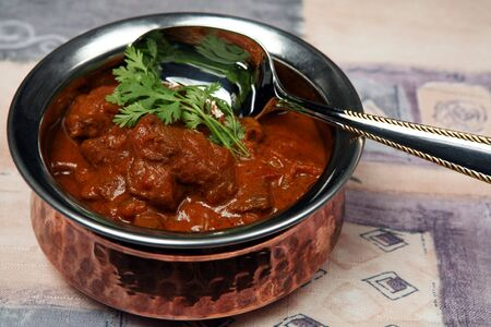 beef curry: A serving bowl full of Madras butter beef curry. Stock Photo