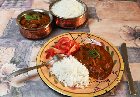 beef curry: A meal of Madras butter beef curry, served with basmati rice and sliced tomato.