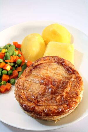 View of an individual pie with boiled potatoes and mixed vegetables photo