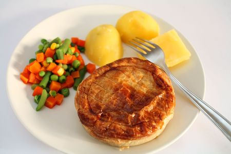 An individual chicken pie with mixed vegetables and boiled potatoes. photo