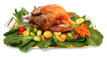 A festive platter, loaded with a roasted turkey and an assortment of delicious vegetables.