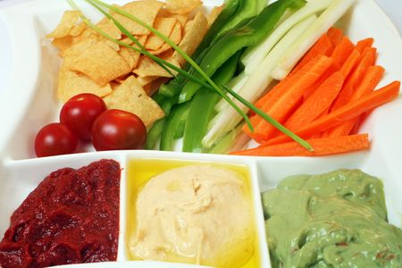 chips and salsa: A plate with salsa, hummus and guacamole dips, julienned vegetables and potato crisps or chips - just right for a party. Stock Photo