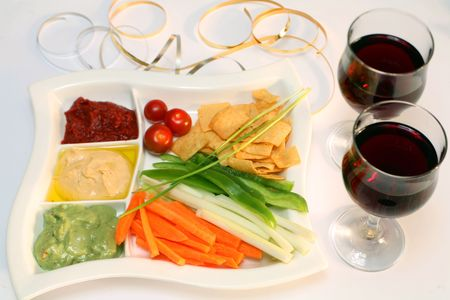 Plate of dips and two glasses of red wine at a party. Stock Photo