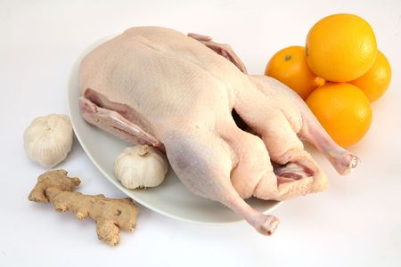 duck: A raw duck with oranges, ginger and garlic, all of which are commonly used in recipes for the bird. Stock Photo