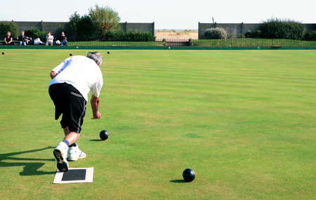unrecognisable: A bowler playing on the village green. Bowls is a traditional British game. The faces of the spectators are unrecognisable. Stock Photo