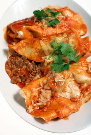 Enchiladas - meat-stuffed tortillas topped with spicy tomato salsa and cheese - on a plate. photo