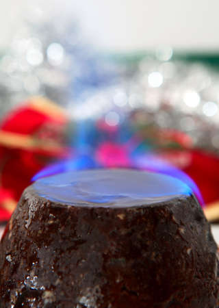 A traditional christmas pudding, smothered in brandy and set alight, with a background of festive festive glitter. photo
