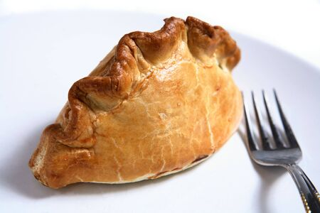 A traditional British Cornish Pasty - a pastry case filled with a thick meat and potato stew - with a fork on a plate. Stock Photo