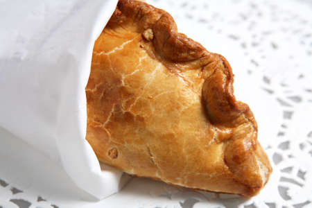 doiley: A traditional English Cornish pasty meat pie, wrapped in a tissue and lying on a paper doiley