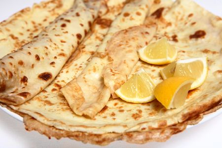 shrove: A pile of English-style pancakes (also called crepes) on a plate with slices of lemon. The pancakes are served, usually with lemon and sugar, on Shrove Tuesday (Mardi Gras) as well as being year-round treat. Stock Photo