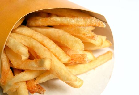 fastfood: A packet of typical fast-food restaurant french fried potatoes or chips. Stock Photo