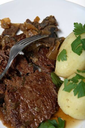 braised mushrooms: A meal of steak braised with onions, mushrooms and herbs, served with boiled new potatoes garnished with chopped Italian parsley. Stock Photo
