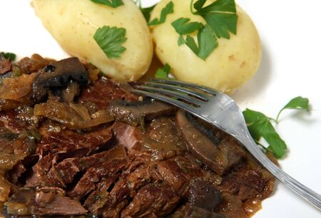 braised mushrooms: A meal of braised beef with onions, mushrooms and herbs, served with boiled new potatoes garnished with chopped Italian parsley. Stock Photo