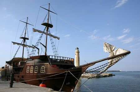 A mock pirate ship, used for tourist pleasure trips from Rethymnon, Crete, a city that was once in fear of the Mediterranean corsairs. The cannon sunk into the quay as a bollard (bottom left) is a genuine relic. photo