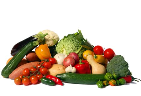 A big display of healthy vegetables isolated on white, including savoy cabbage, cauliflower, vine tomatoes, flow tomatoes, broccoli, green courgette, yellow courgette, jalapeno peppers, leeks, sweet potato, potato, aubergine or eggplant, garlic, red and w