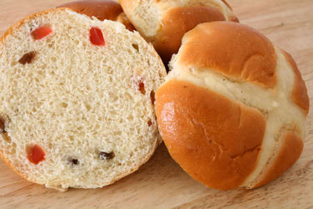 teacake: A hot cross bun - a traditional English teacake that is particularly associated with Easter - sliced ready for toasting, with other buns in the background. Stock Photo