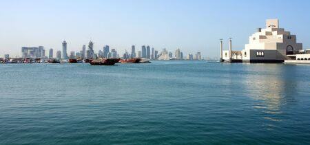 The skyline across Doha Bay in Qatar, with the Islamic museum and dhow harbour in the foreground and the new high-rise district behind.
