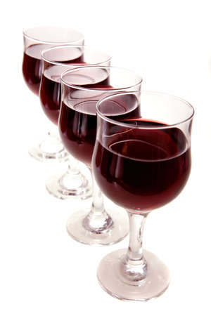 Four glasses of red wine, lined up at an angle, isolated on white. photo