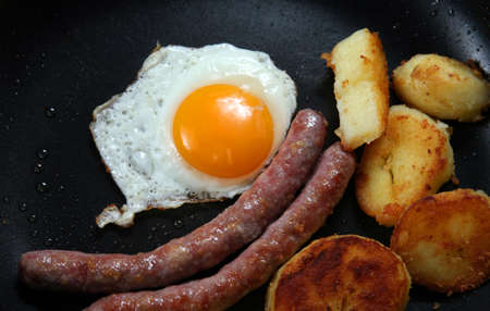 nonstick: A high-calorie breakfast of fried egg, sausages and fried potatoes, close-up in a non-stick pan.
