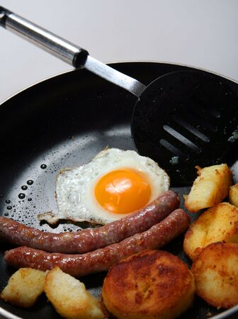 A frying pan with a high-calorie breakfast of sausage, fried potato and fried egg. photo