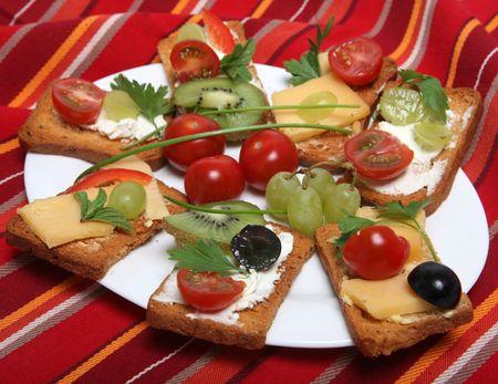 melba: Un plato de galletas (tostadas Melba) con crema o queso duro y adornado con tomates cherry, blanco y negro, uvas, rodajas de pimiento, el kiwi, plana perejil y la menta.