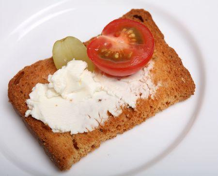melba: A Rusk cubierto con queso crema, tomate y la mitad de una uva como un canape.