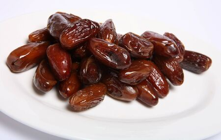 Macro of a plate of sweed dates, the fruit of the date palm, ready to eat. Dates are strongly associated with the Muslim holy month of Ramadan, when they are used to break the fast at the end of each day. photo