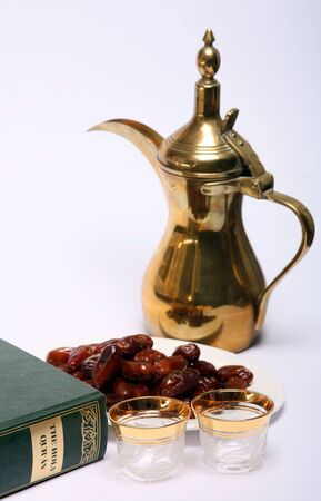 Dates, coffee jug and cups waiting to be filled and a copy of the Holy Quran, all are symbolic of the Muslim fasting month of Ramadan and of the breaking of the fast at Iftar. Stock Photo