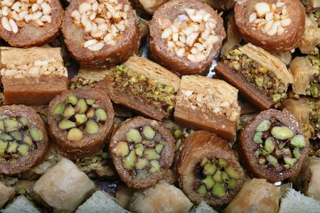 Traditional Arabic sweet pastries, filled with pistachio, cashew or walnuts, baked golden brown and coated with syrup. They are consumed at celebrations, such as the eids or at fast-breaking in Ramadan Stock Photo - 3453644