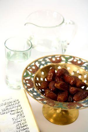 The holy Quran verse about Ramadan with a bowl of dates  - the things used to break the fast at sunset during the Muslim holy month of Ramadan