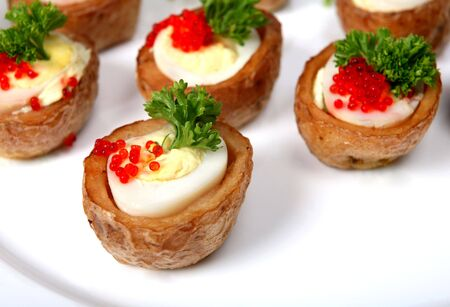 quail egg: A plate of quails egg canapes, the eggs are in tiny baked jacket potatoes, topped with lumpfish caviar and a sprig of english parsley Stock Photo