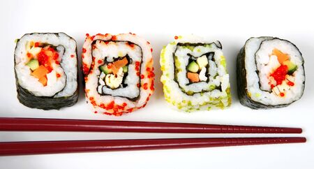 Japanese nori-wrapped futomaki (at each end) and rice-wrapped uramaki (California roll) sushi rolls on a white plate with chopsticks Stock Photo