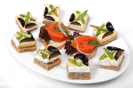 A plate of Brie cheese on toast canapes and smoked salmon on bread  photo