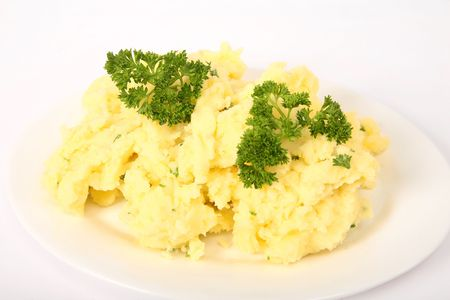 creamed: A serving plate of creamed parsley potatoes on a plain background.