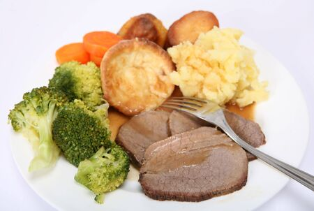 mashed potatoes: A dinner of slices of braised (pot-roasted) beef, broccoli, carrots,mashed potato,roast potato,   English Yorkshire puddings and gravy. Stock Photo