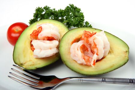 An avacado (guacamole) boat filled with prawns, served with a cherry tomato and parsley garnish photo