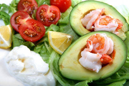 shrimp: Prawns (or shrimps) in avacado (or guacamole) boats, with a lettuce and tomato salad, mayonnaise and lemon wedges Stock Photo