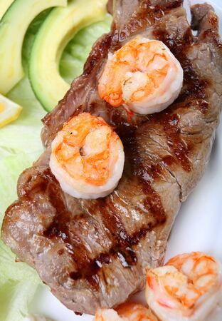 Surf and turf grilled New York steak with prawns, viewed from above, with a salad of guacamole and lettuce photo